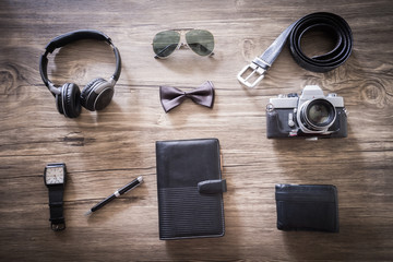 Men's casual outfits with accessories on on wood background with