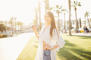 A model girl with a sunglasses is posing to the camera. A female with a brown hairs wearing striped shirt is smiling while standing in a city park on a sunny day.