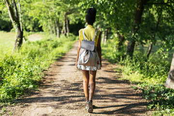 Back view of young woman with backpack in nature