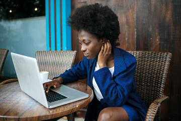 Young woman working with laptop in a street cafe