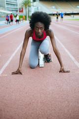 Young black athlete preparing for race in stadium