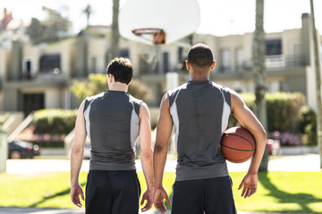 Rear view of two basketball players outdoors