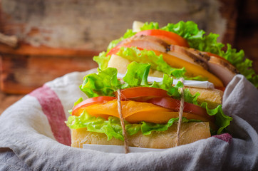 Homemade sandwich with fresh tomatoes and chicken breast in basket on wooden background. Selective focus. Picnic concept