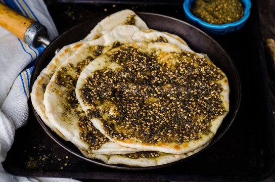 Freshly baked flatbread with mixed spice and herbs - zaatar or zatar on vintage wooden background. Selective focus. Toned image