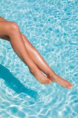 jambes de femme dans l'eau d'une piscine