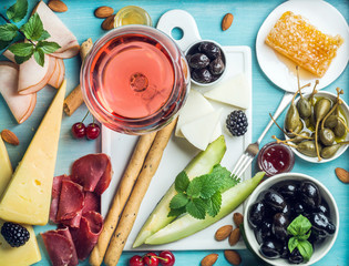 Summer wine snack set. Glass of rose, meat, cheese, olives, honey, bread sticks, nuts, capers and berries with white ceramic board in center, blue wooden background