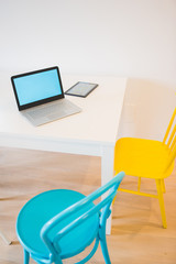View of desk with tablet and pc with colorful chairs