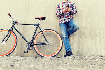 close up of hipster man with smartphone and bike