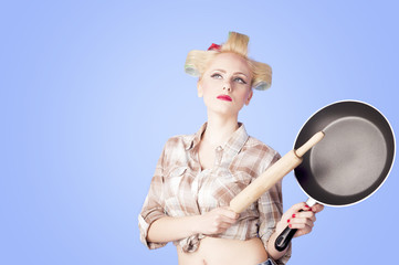 Pinup housewife portrait with pan and roll pin