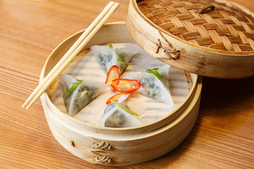 Dim sums with spinach and tofu cheese in asian restaurant