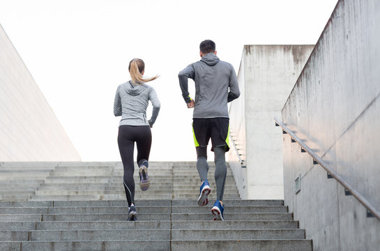 couple running upstairs on city stairs