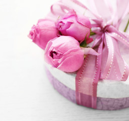 Gift box with beautiful roses on wooden background