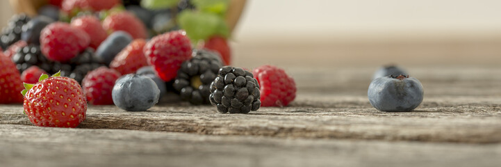 Mixed berry fruits scattered on a wooden desk