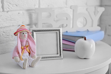 Toy rabbit with frame on white wall background