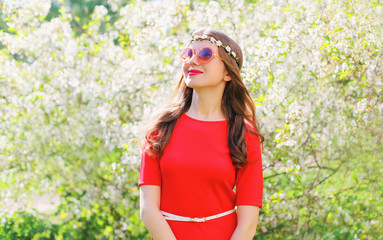 Beautiful smiling woman in red dress looks with hope up over spr