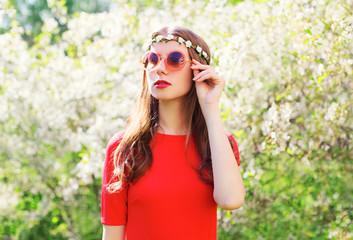Fashion beautiful hippie woman in a spring flowering garden