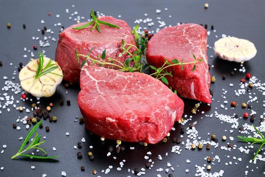 Fresh Raw Beef steak Mignon, with salt, peppercorns, thyme, garlic.