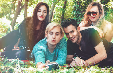 Group of smiling friends with smartphone sitting on grass and making selfie in park