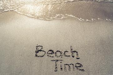 Beach time hand drawn lettering text on sand. Sunburst