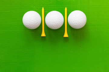 Golf balls and wooden golf tees on the green table