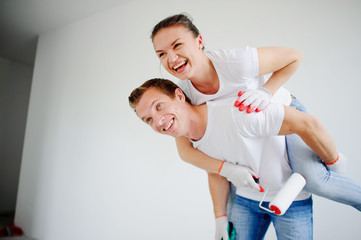 The young couple has fun doing repair in the apartment.