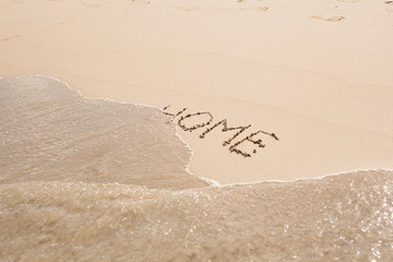 word home written in sand on beach