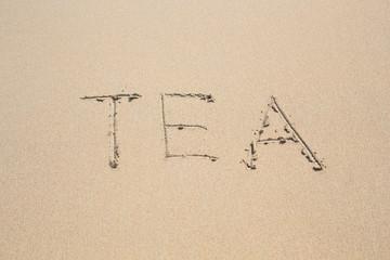 word tea written in sand on beach