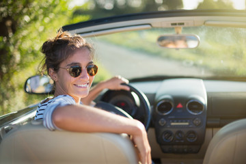 Rear view. A young woman happy to drive her convertible car