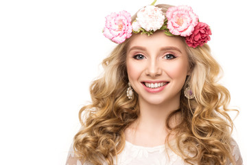 Beautiful girl with wreath of pink flowers, long curly blond hair and beautiful smile