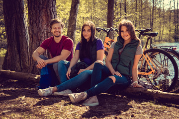 Smiling male with two attractive females relaxing in a forest.