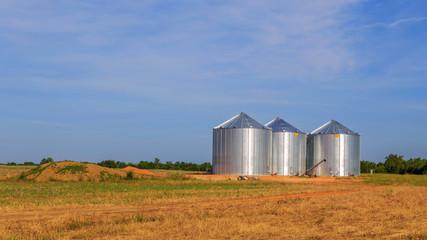 Triple Stainless Steel Grain Silo: Three adjacent stainless steel silos in an open field just off highway 80 in Demopolis, AL