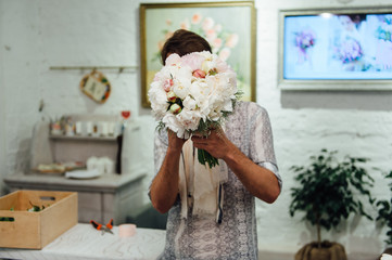 Male florist preparing bouquet of peones
