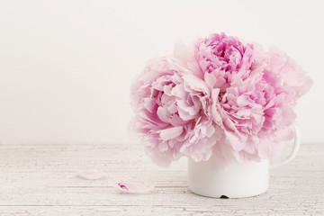 beautiful pink peonies in an enamel mug on a wooden desk, copyspace
