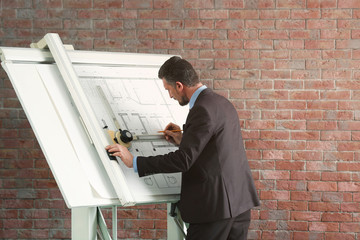 Engineer working with blueprint on panel board indoors