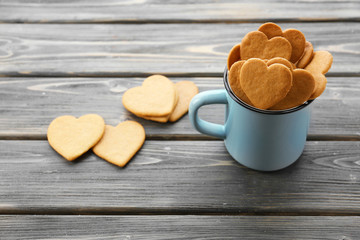 Heart shaped biscuits in metal mug on wooden background