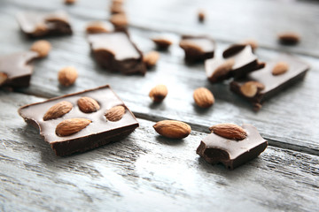 Chocolate pieces with nuts on wooden background
