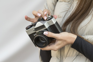 the girl with the French manicure is holding the vintage  camera