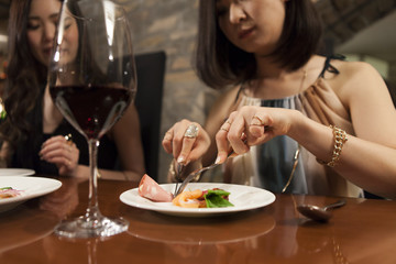 Young women are enjoying the meal with a glass of wine