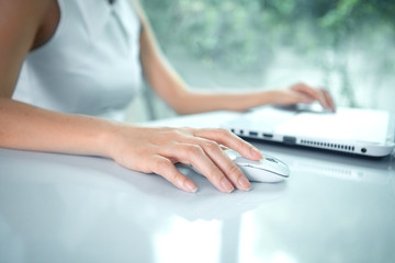 Female hand with computer mouse on table