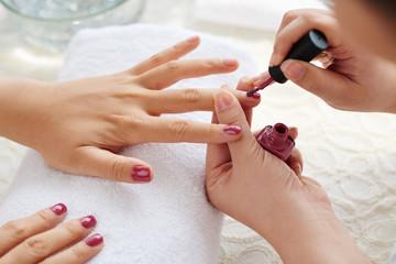 Master applying polish on fingernails on woman