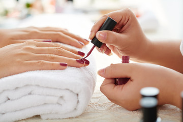 Fotobehang Manicure Side view of manicurist applying marsala nail polish