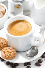 cup of espresso and cookies on a white table, vertical, closeup