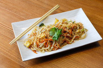 Rice noodles with tofu and vegetables  in rectangle plate  in asian restaurant