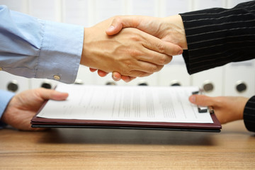 business partners are handshaking and exchanging contract after