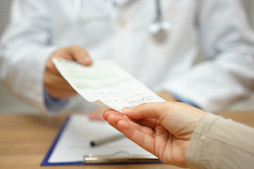 doctor is giving a prescription to a female patient