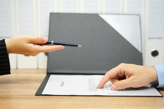 businesswoman offer a pen over a contract to client