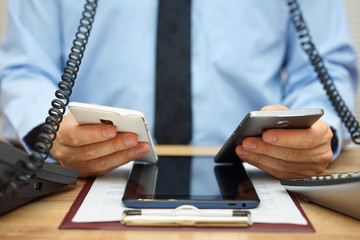 busy businessman in office at the desk using two mobile phones,