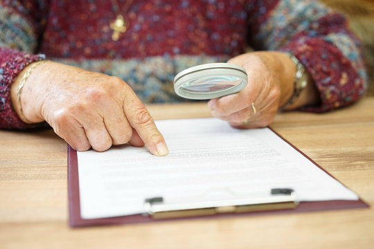 elderly person with magnifying glass checking document
