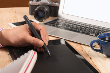Photographer drawing and retouching image on laptop computer, using a digital tablet and stylus pen. Closeup of man's hand with dslr camera in background. Copy space in foreground