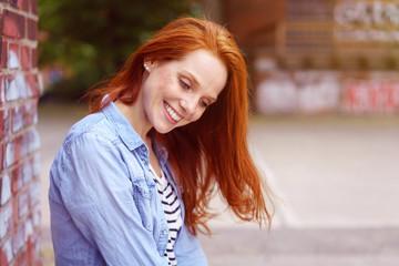 frau sitzt draußen in der stadt und schaut lächelnd nach unten